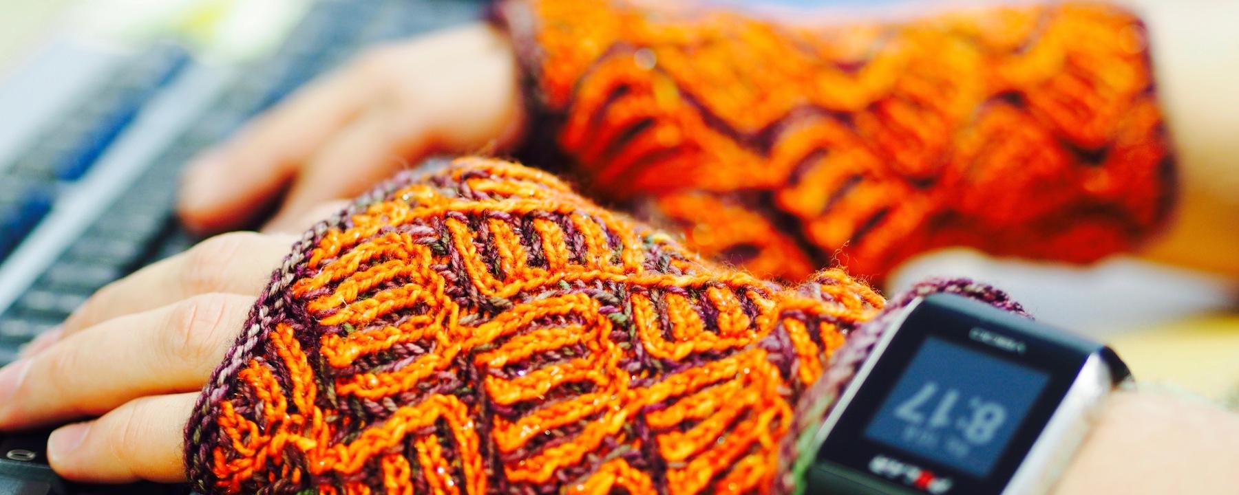 Allisonin sormettomien malliksi joutui pahaa aavistamaton miespuolinen (sirokäsinen) työtoveri. Langat ovat Handun Gimalletta (oranssi) ja Lanitum ex machinan käsinvärjättyä ohutta sukkalankaa. Kuva Susa Junnola, Moreeni 2016.